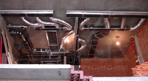Выполненный монтаж воздуховодов и щелевых диффузоров в помещении двухуровневой квартиры