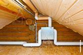 Фото вытяжного вентилятора Аэрэко VAM и воздуховодов на чердаке деревянного загородного дома