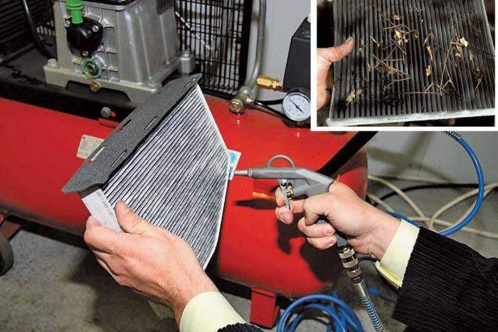 На фото мастер сервиса продувает радиатор кондиционера сжатым воздухом.