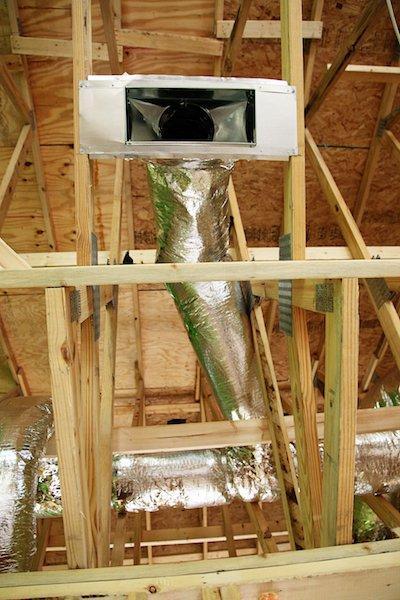 Вентиляционный диффузор и воздуховоды размещенные в потолочных балках при возведении каркасного дома с сауной.